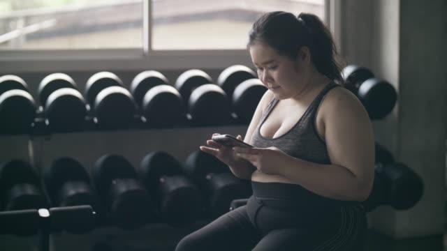 ジムでスマートフォンを使用して女性 - 体育館点の映像素材/bロール