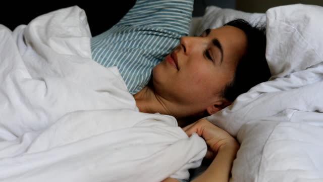 kvinna med mobiltelefon efter att vakna upp på sängen - endast en kvinna i 30 årsåldern bildbanksvideor och videomaterial från bakom kulisserna