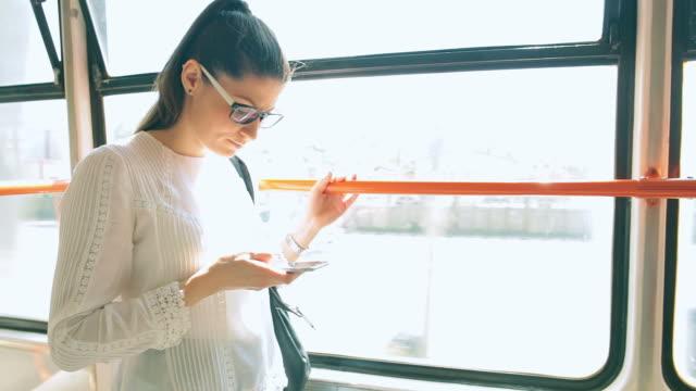 stockvideo's en b-roll-footage met vrouw met behulp van slimme telefoon terwijl het reizen met het openbaar vervoer. - cross processen