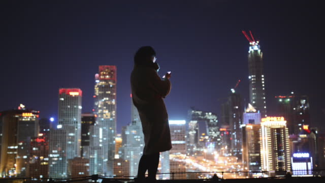 female using smartphone in city at night - city life stock videos & royalty-free footage