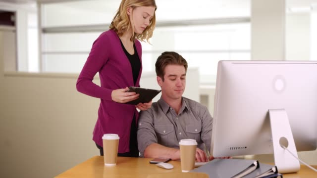 female using touchpad device standing behind male colleague working on computer - touchpad stock videos & royalty-free footage
