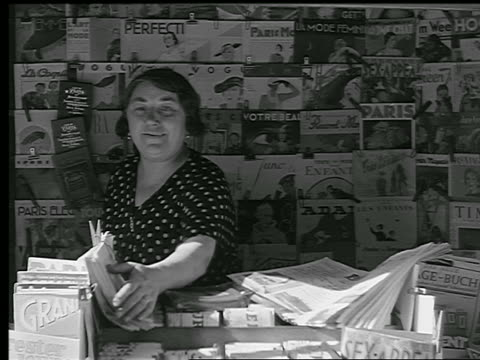 vidéos et rushes de b/w 1936 female vendor inside kiosk straightening newspapers / magazines on wall behind her / paris - kiosque à journaux