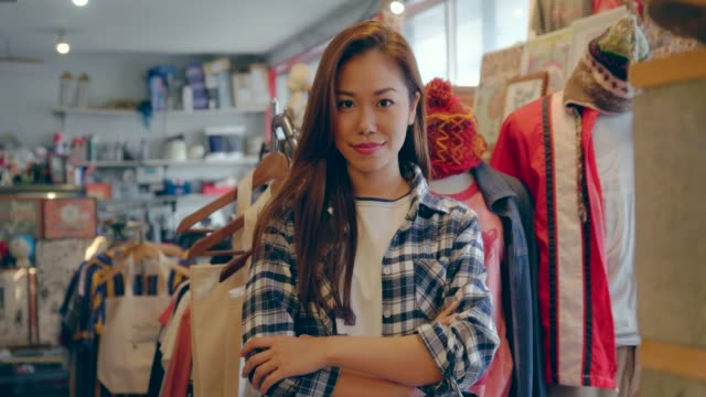female vintage clothes shops owner looking at camera. - garment stock videos & royalty-free footage