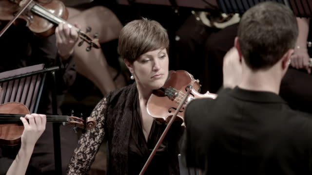 female violin player watches conductor - musical conductor stock videos & royalty-free footage