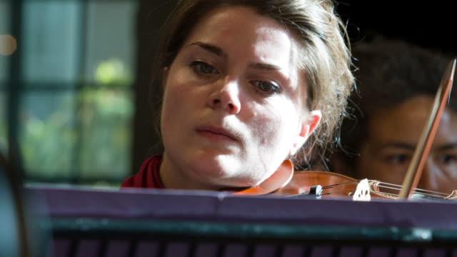 Weibliche Geiger im Orchester spielt