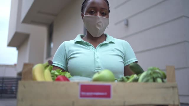 female volunteer black ethnicity holding a crate with fresh vegetables to deliver for people in need during coronavirus pandemic - crucifers stock videos & royalty-free footage
