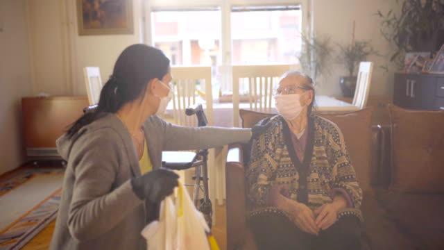 female volunteer bringing groceries to a senior woman at home - glove video stock e b–roll