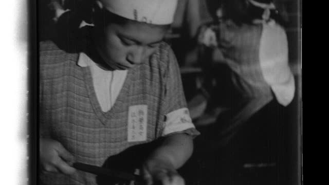 female volunteer corps students from the kasukabe girls' high school wear hachimaki headbands as they assemble airplanes in a factory. - headband stock videos & royalty-free footage