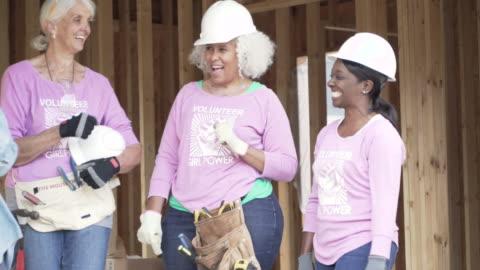 vídeos y material grabado en eventos de stock de female volunteer workers on a construction site - caridad y auxilio
