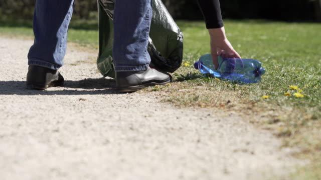 female walker picking up litter in public park - littering stock videos & royalty-free footage