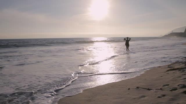 W/S Female walking along beach at sunset