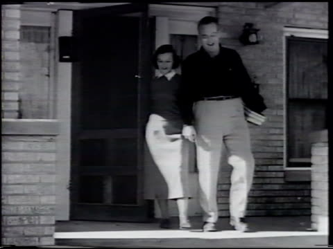 female walking out of house w/ adult male holding her hand holding books in other male w/ female outside house one child on tricycle w/ boy running... - young war veteran stock videos & royalty-free footage