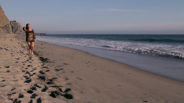 female walks along beach. - dress stock videos & royalty-free footage