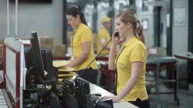 Female warehouse employee answering the phone at the office desk in the warehouse