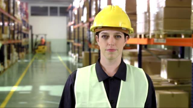 Weibliche Warehouse Mitarbeiter erinnert an die Kamera