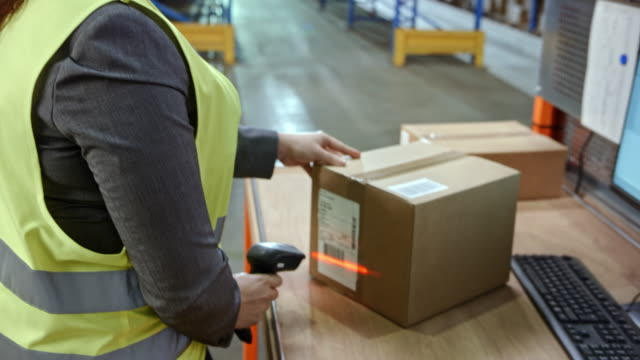 female warehouse employee scanning packages on a desk in the warehouse with a handheld scanner - distribution warehouse stock videos & royalty-free footage