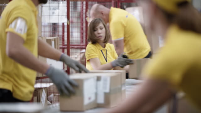 ld female warehouse employee taking packages off the conveyor belt and stacking them - postal worker stock videos & royalty-free footage