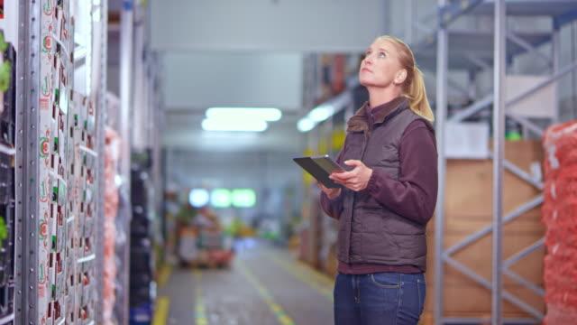 ds impiegato di magazzino femminile a piedi in una navata del magazzino e controllare i prodotti freschi - scienza e tecnologia video stock e b–roll
