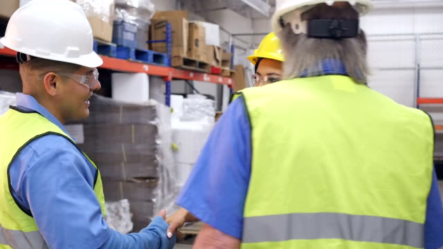Female warehouse manager shaking hands with male coworkers during meeting
