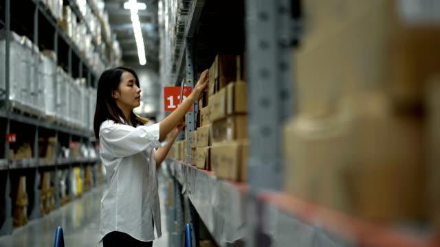 棚の上の商品をチェックする4k女性倉庫労働者 - 貯蔵庫点の映像素材/bロール
