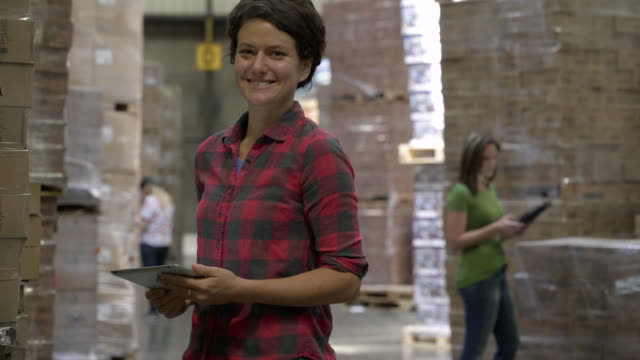 Female warehouse worker holding and writing on clipboard by stock