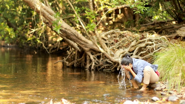Female Washing Face with River Water
