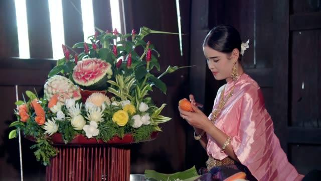 vídeos y material grabado en eventos de stock de mujer con ropa tradicional tailandés vestido talla de zanahoria para la decoración - arte decorativo