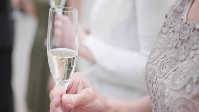 SLO MO Female wedding guest holding a glass of sparkling wine