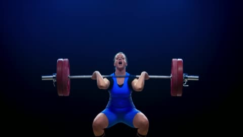 female weightlifter in blue outfit performing the clean and jerk lift at the competition - weight training stock videos & royalty-free footage