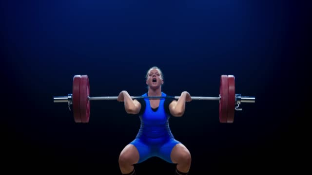 female weightlifter in blue outfit performing the clean and jerk lift at the competition - picking up stock videos & royalty-free footage