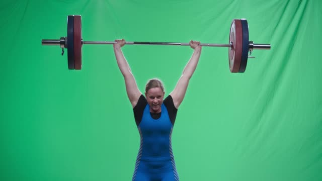 female weightlifter in blue outfit performing the clean and jerk lift - potere femminile video stock e b–roll