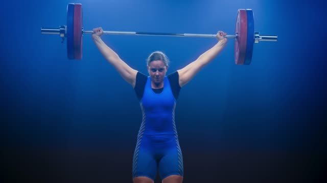 female weightlifter lifting the barbell at a competition performing the snatch lift - picking up stock videos & royalty-free footage