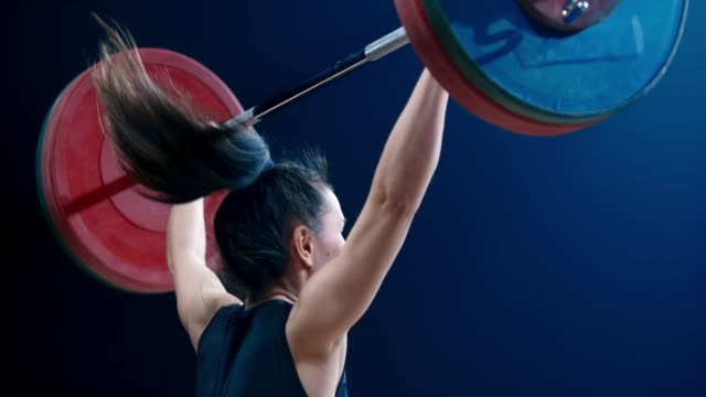 slo mo tu female weightlifter performing a snatch lift at a competition - resistenza concetto video stock e b–roll