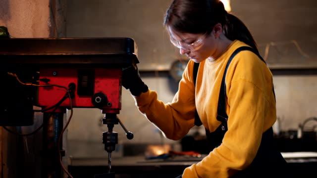 female welder drill a metal - imprenditore video stock e b–roll