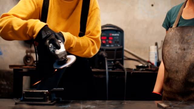 vídeos de stock, filmes e b-roll de soldador feminino moagem barra de ferro com serra elétrica - trabalhador manual