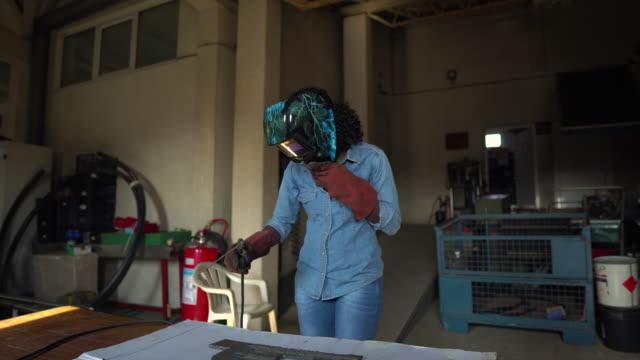 vídeos de stock, filmes e b-roll de soldador fêmea na oficina - soldar