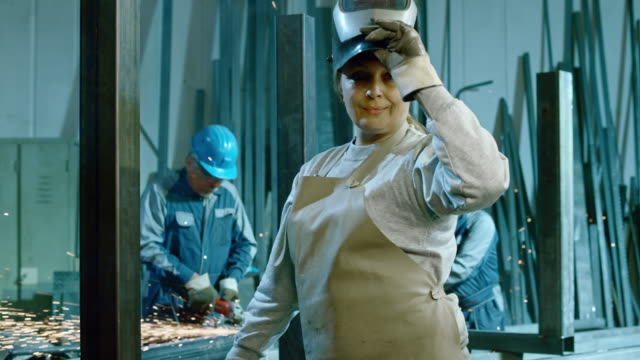 SLO MO DS Female welder portrait in a workshop
