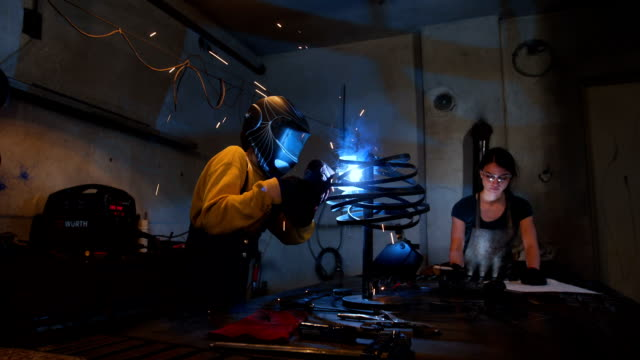 female welder with welding mask using welding machine - welding stock videos & royalty-free footage