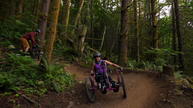 vídeos de stock e filmes b-roll de ts female wheelchair athlete on adaptive mountain bike following friend down trail - cadeira de rodas