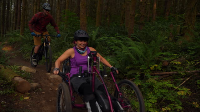 ts female wheelchair athlete on adaptive mountain bike riding down trail with friends - mid adult women stock videos & royalty-free footage