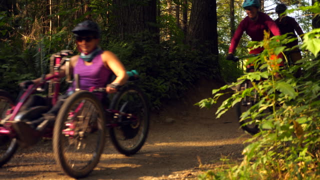 ms female wheelchair athlete riding adaptive mountain bike on trail with friends - disability stock videos & royalty-free footage