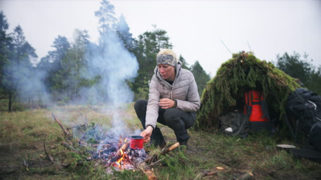 ds female wilderness survival expert cooking a meal by the fire in nature - survival stock videos & royalty-free footage