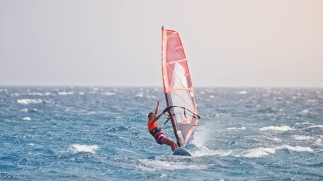 SLO MO Female windsurfer riding across the waves