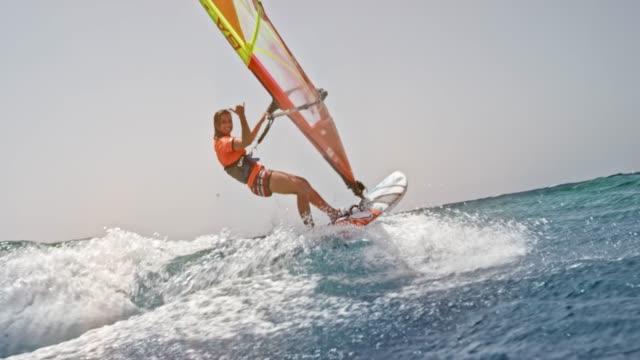 stockvideo's en b-roll-footage met slo mo vrouwelijke windsurfer rijden in zon en zwaaien naar de camera - windsurfen