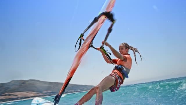 SLO MO Female windsurfer smiling while riding in sunshine