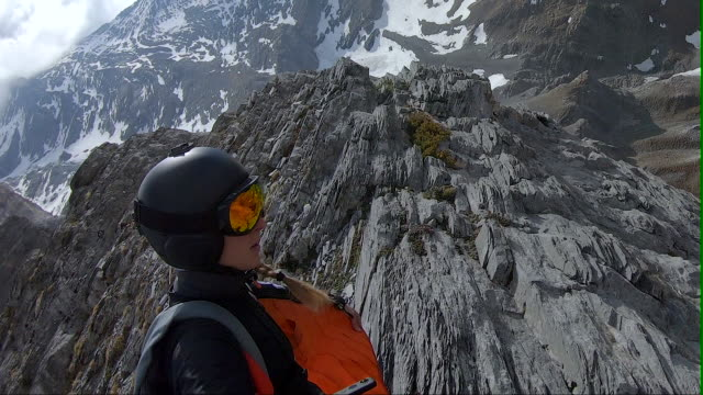 female wingsuit flier leaps from cliff, then descends past mountain peaks - mountain peak stock videos & royalty-free footage