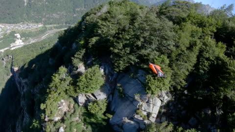 female wingsuit flier sails along cliffs in the mountains - exalterande bildbanksvideor och videomaterial från bakom kulisserna