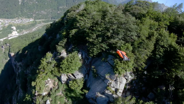 female wingsuit flier sails along cliffs in the mountains - extreme terrain stock videos & royalty-free footage