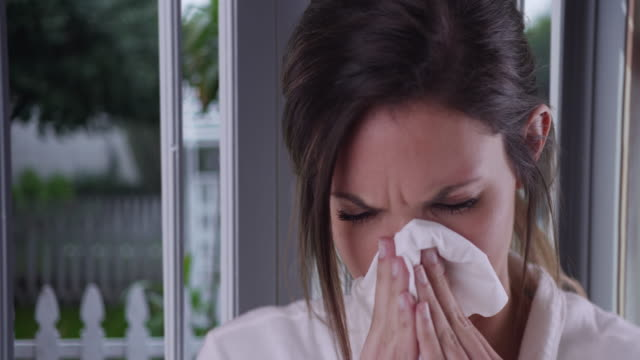 female with cold or allergies wiping nose with tissue inside house by window - tissue paper stock videos and b-roll footage