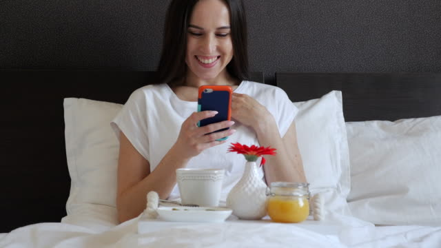 Female with phone sitting with service tray in bed